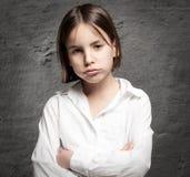 Kleines Mädchen mit gebohrtem Ausdruck Stockfotos