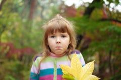 Kleines Mädchen mit gefallenen Blättern Stockbild