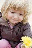 Kleines Mädchen mit gelber Blume Stockfotos