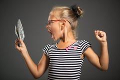 Kleines Mädchen mit Geld lizenzfreies stockfoto