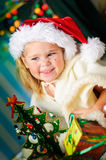 Kleines Mädchen mit Geschenk und Weihnachtsbaum stockfoto