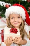 Kleines Mädchen mit Geschenk- und Weihnachtshut Stockfotos