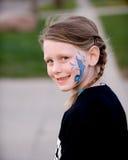 Kleines Mädchen mit Gesichts-Farbe Lizenzfreie Stockfotografie