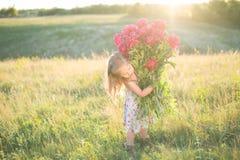 Kleines Mädchen mit großem Blumenstrauß Stockfotos