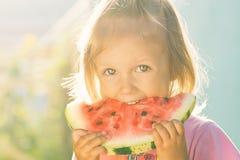 Kleines Mädchen mit großen schönen Augen eine Wassermelone essend Lizenzfreie Stockfotografie