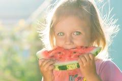 Kleines Mädchen mit großen schönen Augen eine Wassermelone essend Stockfoto