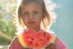 Kleines Mädchen mit großen schönen Augen eine Wassermelone essend Stockfotos