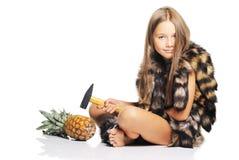 Kleines Mädchen mit großer Ananas und Hammer Stockfoto