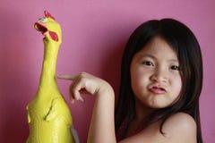 Kleines Mädchen mit Gummihuhn Stockfotos