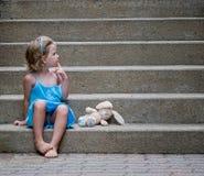 Kleines Mädchen mit Häschen auf konkreten Schritten Stockbilder