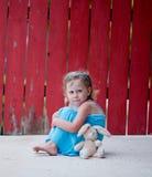 Kleines Mädchen mit Häschen nahe bei rotem Zaun Stockfotos