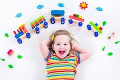 Kleines Mädchen mit hölzernem Zug Stockfotos