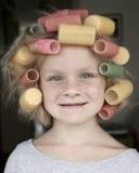 Kleines Mädchen mit Haar-Rollen lizenzfreie stockbilder