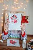 Kleines Mädchen mit handgemachter Weihnachtspostkarte Stockfotos