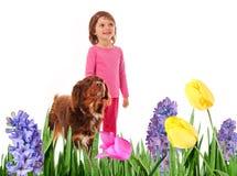 Kleines Mädchen mit Hundeim Frühjahr Garten stockfotografie