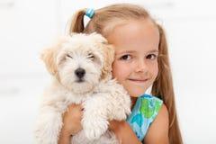 Kleines Mädchen mit ihrem flaumigen Hund stockfotografie