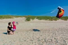 Kleines Mädchen mit ihrer Mutter, die einen Drachen auf dem Strand spielt Stockfotos
