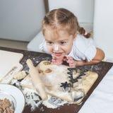 Kleines Mädchen mit ihrer schmutzigen Nase hilft ihrer Mutter, Mehlklöße zu machen stockfotografie