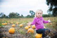 Kleines Mädchen mit Kürbisen Stockbilder