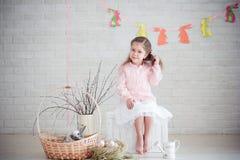 Kleines Mädchen mit Kaninchen und Ostern-Dekorationen Lizenzfreie Stockfotografie
