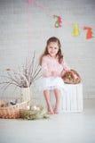 Kleines Mädchen mit Kaninchen und Ostern-Dekorationen Stockfoto
