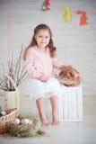 Kleines Mädchen mit Kaninchen und Ostern-Dekorationen Stockbilder