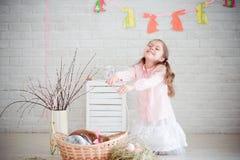 Kleines Mädchen mit Kaninchen und Ostern-Dekorationen Stockbild