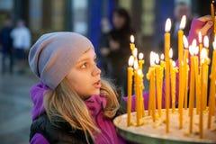 Kleines Mädchen mit Kerzen in der orthodoxen russischen Kirche Lizenzfreies Stockfoto