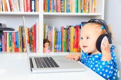 Kleines Mädchen mit Kopfhörern und Laptop Lizenzfreie Stockfotografie