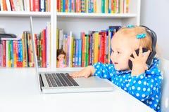 Kleines Mädchen mit Kopfhörern und Laptop Lizenzfreie Stockbilder