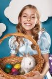Kleines Mädchen mit Korb mit Farbeiern und weißem Osterhasen Lizenzfreies Stockbild