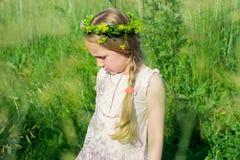 Kleines Mädchen mit Kranz von Wildflowers auf ihrem Kopf Stockfoto