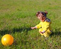 Kleines Mädchen mit Kugel auf Wiese Stockbild