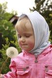 Kleines Mädchen mit Löwenzahnborduhr stockfoto