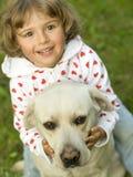 Kleines Mädchen mit Labrador-Apportierhund Stockfotografie