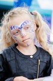 Kleines Mädchen mit langer blonder angebundener Haar- und Gesichtsmalerei Stockfotos
