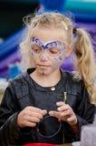 Kleines Mädchen mit langer blonder angebundener Haar- und Gesichtsmalerei Stockbilder