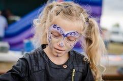 Kleines Mädchen mit langer blonder angebundener Haar- und Gesichtsmalerei Lizenzfreie Stockbilder