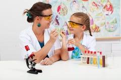 Kleines Mädchen mit Lehrer in der grundlegenden Wissenschaftsklasse Stockfotos