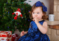 Kleines Mädchen mit Lutscher und Weihnachtsbaum und Dekoration Stockfotos