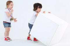 Kleines Mädchen mit Medaille auf Kasten Blicke am Jungen bewundernd Stockfotografie