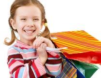 Kleines Mädchen mit mehrfarbigen Paketen Stockfotografie