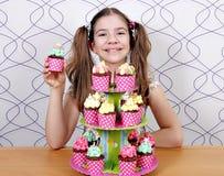 Kleines Mädchen mit Muffinkuchen Stockfotografie