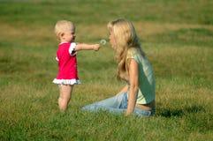 Kleines Mädchen mit Mutter Stockfotos