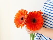 Kleines Mädchen mit orange Blumen Stockfotos