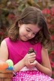 Kleines Mädchen mit Ostern-Korb, der mit Küken spielt Lizenzfreies Stockfoto