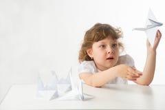 Kleines Mädchen mit Papierkränen Stockfotografie
