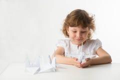 Kleines Mädchen mit Papierkränen Stockfotos