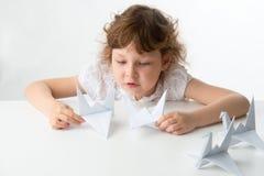 Kleines Mädchen mit Papierkränen Stockbild