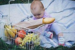 Kleines Mädchen mit Picknickkorb im Sommerpark stockfoto